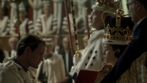 Prince Philip, Duke of Edinburgh kneeling before his wife, the Queen at her coronation in 1953 as portrayed by Claire Foy and Matt Smith in The Crown on Netflix.